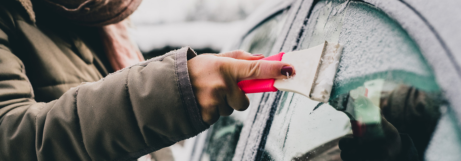 woman scraping ice off of car window