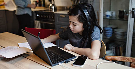 kid wearing headphones and working with laptop