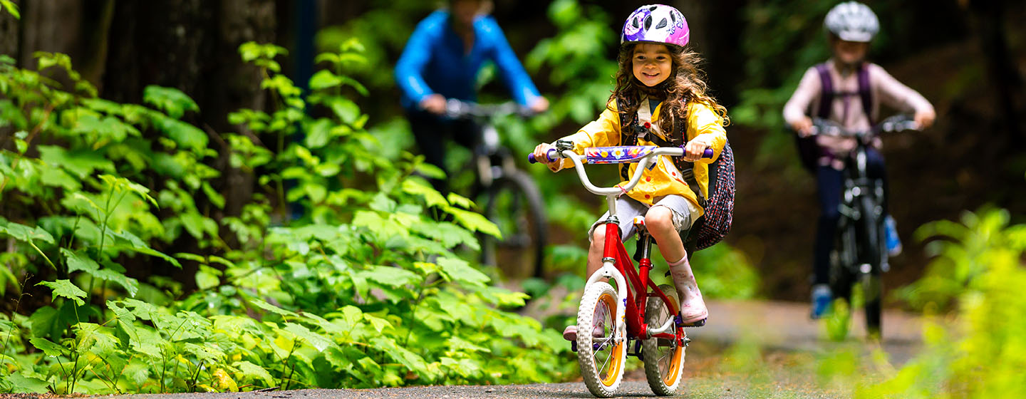 young girl cycling on trail
