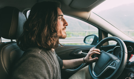 Man with long hair driving