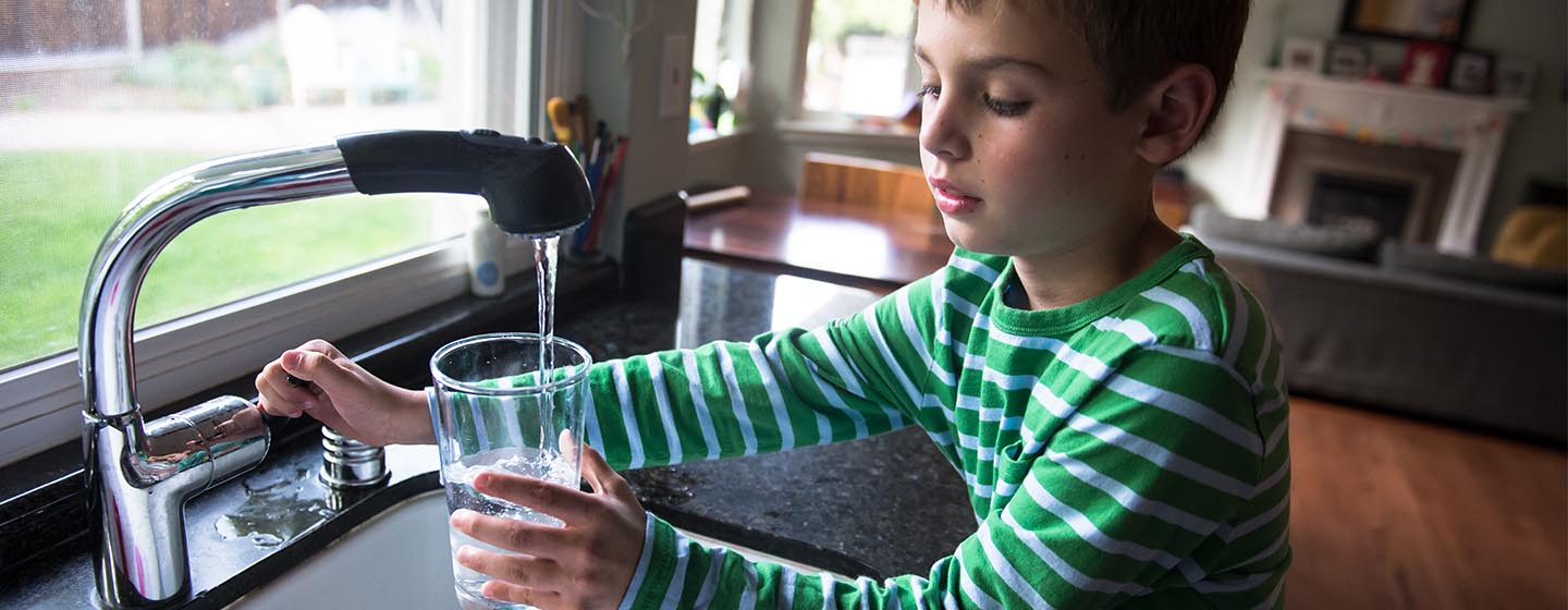 boy filling glass with kitchen sink tap water