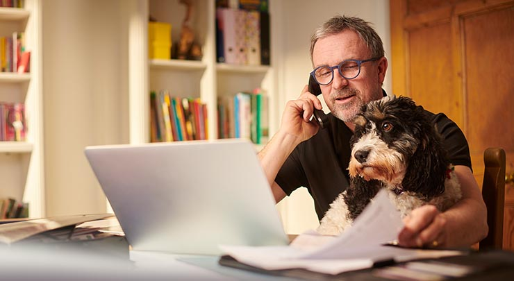 older man on laptop and phone with dog beside him
