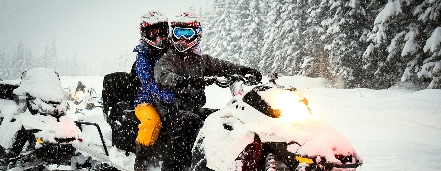 riders on snow mobile