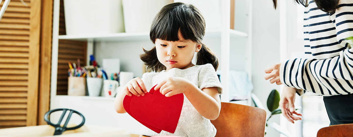 girl making heart shaped craft