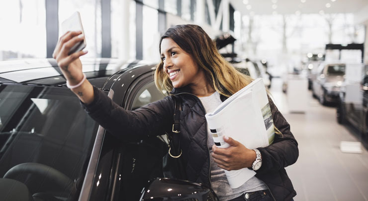 woman taking selfie with new car mobile