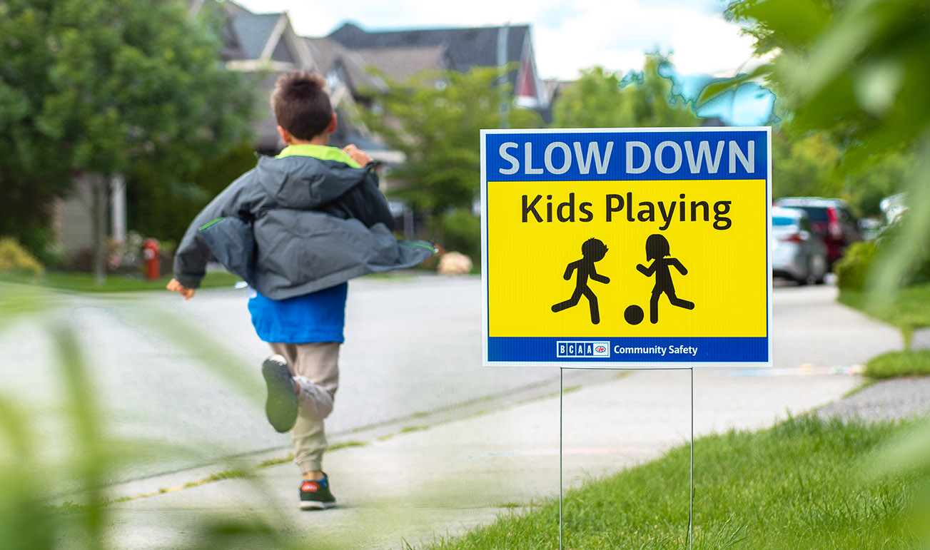 boy runs by slow down kids playing lawn sign